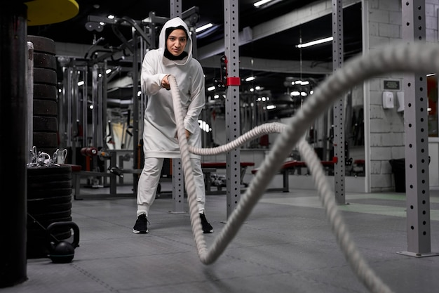 Strong arabic sportswoman working out in functional training gym doing crossfit exercise with battle ropes, wearing sportive hijab. cross-fit workout motivation