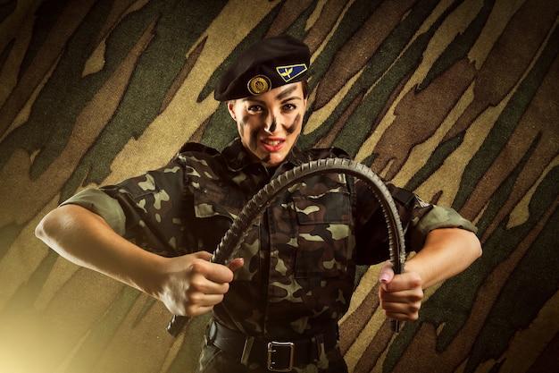 強い陸軍兵士の女性が鉄の棒を曲げている