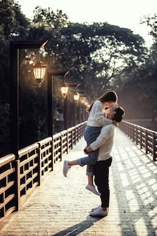 The strong asian man hold up his girlfriend at the bridge with lamp all the way.