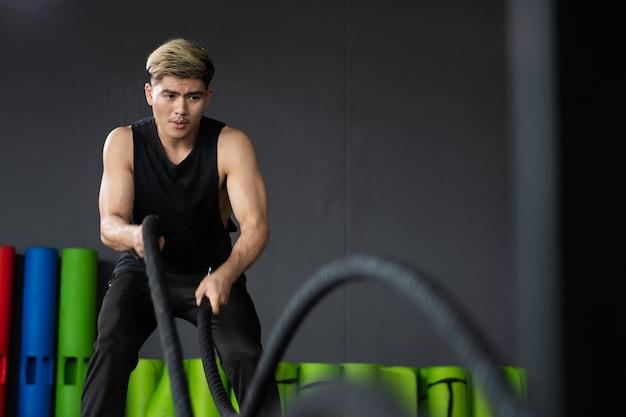コピースペースのある屋内ジムでバトルロープエクササイズをする準備ができた位置に立っている強いアジアのスポーティーな男。ボディービルの概念、筋肉の構築を訓練する強力な若いスポーツマン。
