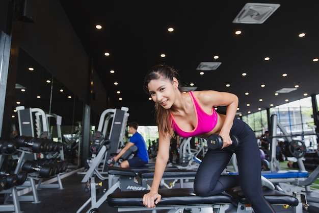 Strong asian woman exercising in the fitness gym. athlete training lifting dumbbell, copy space. fitness work out and yoga healthy concept