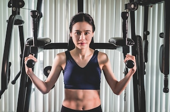 Strong asian woman is training on fitness gym machine