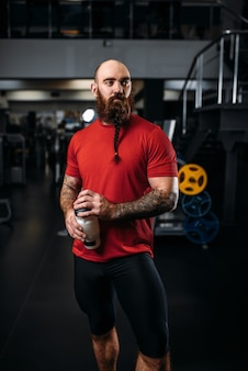 Strong athlete drinks water, workout in gym