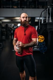 Сильный спортсмен пьет воду, тренировки в тренажерном зале