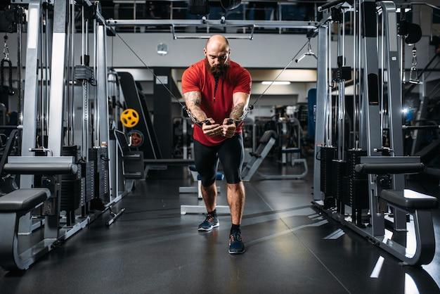 スポーツウェアの強いアスリート、ジムのエクササイズマシンでトレーニング。