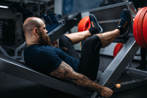 Сильный спортсмен на тренажере со штангой