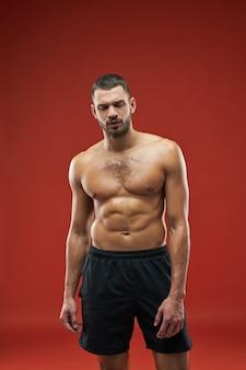 빨간색 배경에 격리된 검은색 운동복을 입고 사진 카메라에서 포즈를 취하는 강한 운동선수