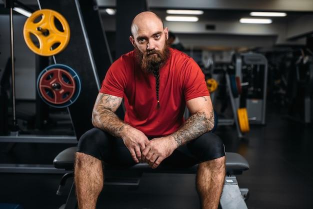 Сильный спортсмен сидит на скамейке, тренировки в тренажерном зале.