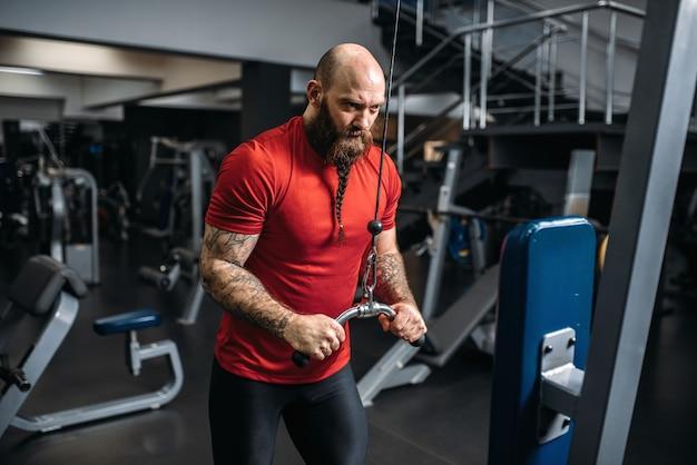 強いアスリート、エクササイズマシンでトレーニング