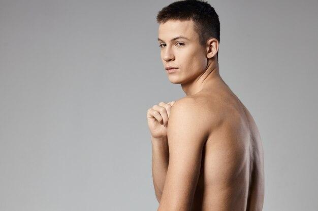 膨らんだ腕の筋肉と裸の背中灰色の背景を持つ強いアスリート