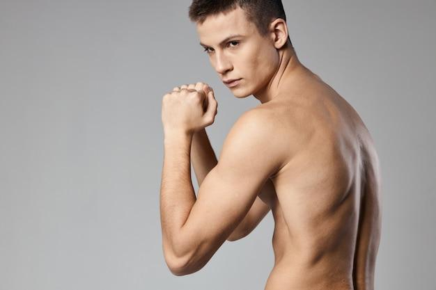 腕の筋肉が裸で膨らんでいる強いアスリート