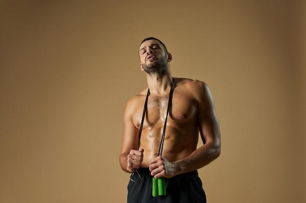 Сильный спортсмен с мощным торсом держит скакалку на плече, изолированную на желтом фоне