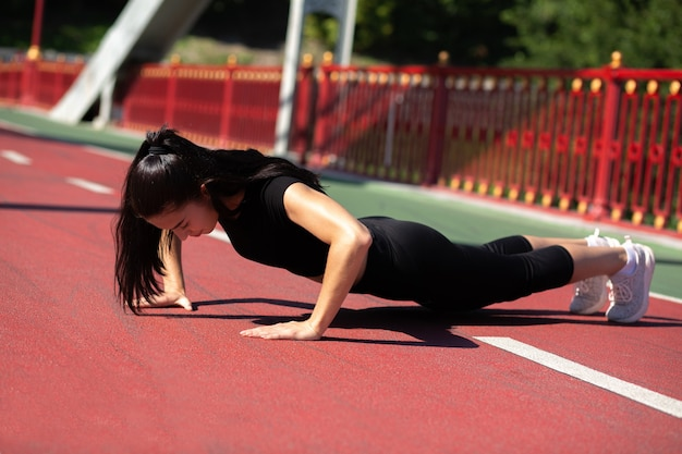 Strong athlete woman doing plank exercise outdoor at the bridge in sunny morning