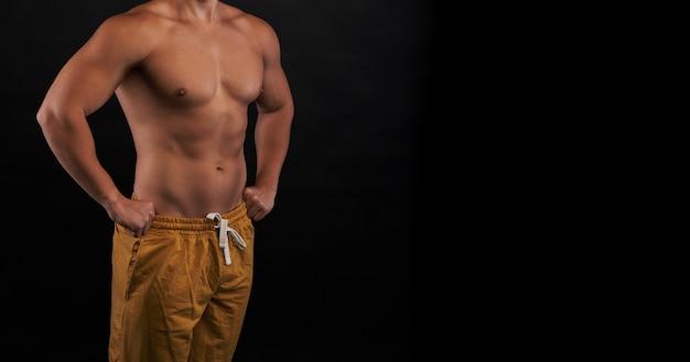 검은 색 바탕에 강한 운동 몸. 피트니스 광고 텍스트를위한 여유 공간입니다. 완벽한 구호 몸통의 초상화. 스포츠 용품 광고에 좋은 샷.