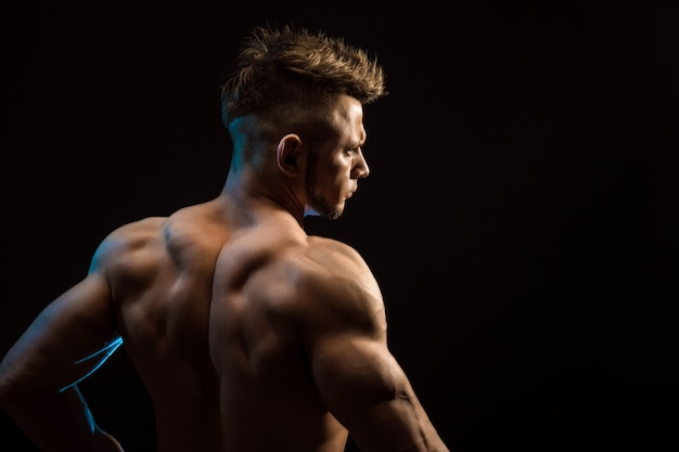 Strong athletic fitness man posing back muscles, triceps, latissimus over black background