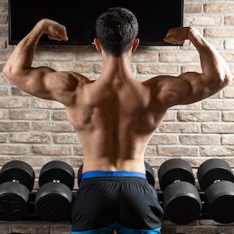 背中の筋肉、ジムで上腕三頭筋をポーズする強い運動選手のフィットネスモデル