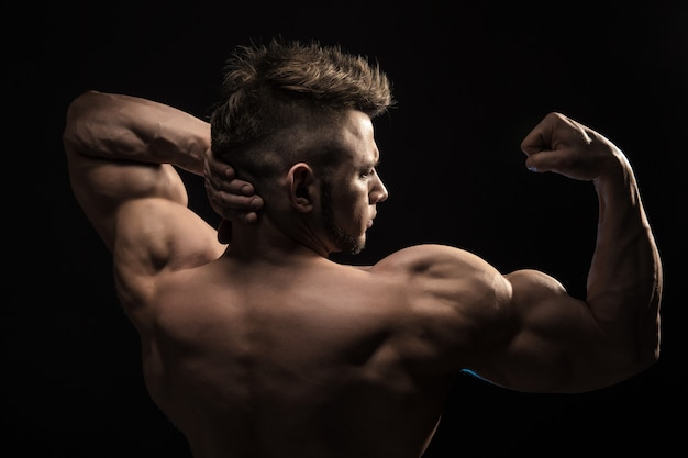 Strong athletic man fitness model posing back muscles.