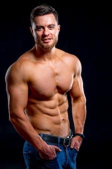 Сильный атлетический торс модели фитнеса человека показывая 6 abs пакета. изолированные на темном фоне. фото половинной длины.