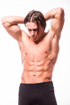 白い壁に分離された胴体を曲げる強い運動選手