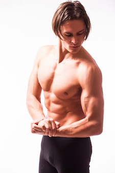 Strong athletic man flexing torso isolated on white wall