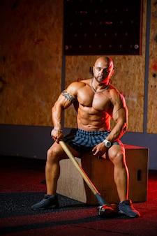 ジムの背景にスポーツハンマーでポーズをとる強い運動選手。完璧な腹筋、肩、上腕骨、三頭筋、胸を備えた強力なボディビルダー。