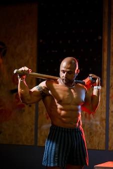 Сильный спортивный мужчина позирует со спортивным молотком на фоне тренажерного зала. сильный бодибилдер с идеальным прессом, плечами, бицепсами, трицепсами и грудью.