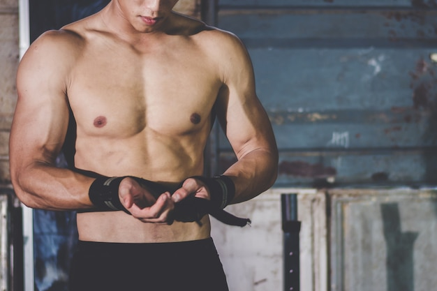 Strong athletic man showing muscel in local gym