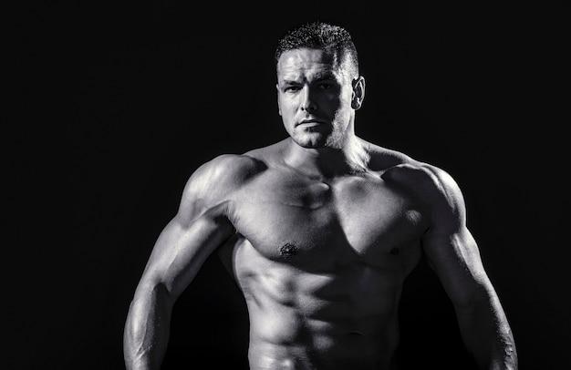Сильный атлетичный мужчина, показывающий мускулистое тело и пресс с шестью упаковками. показаны мускулистый торс. черное и белое.