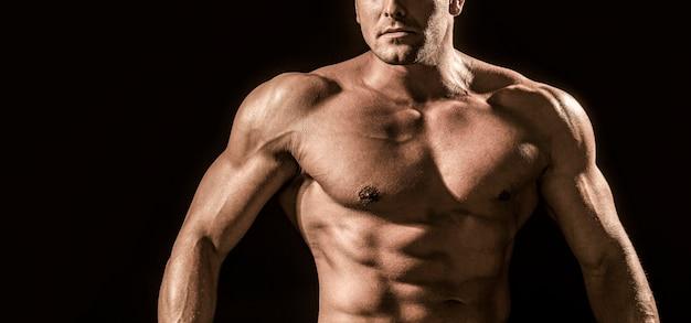 筋肉質の体と6パックの腹筋を示す強い運動選手。筋肉質の胴体を示しています。