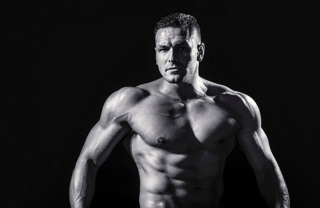 Strong athletic man showing muscular body and sixpack abs. showing muscular torso. black and white.