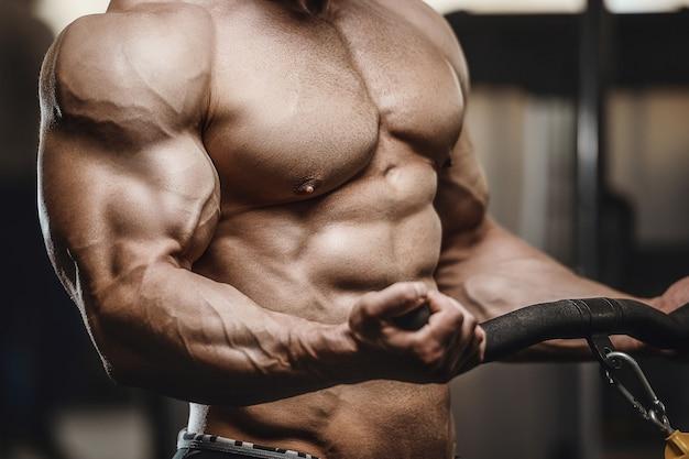 ジムでトレーニングエクササイズをしている筋肉をポンピングする強い運動男性がクローズアップ