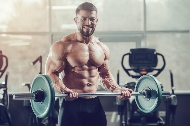 ジムでトレーニングエクササイズをしている筋肉をポンピングする強い運動男性