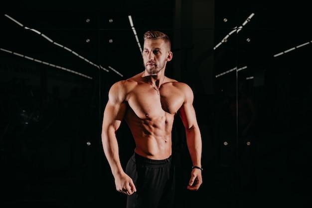 Сильный спортивный мужчина без рубашки на черном фоне