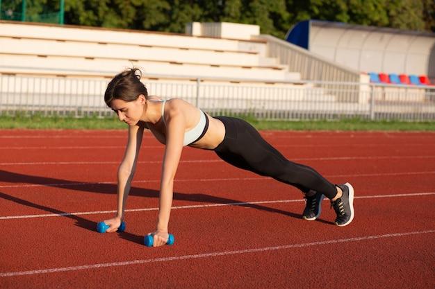 경기장에서 아령으로 운동을 하는 운동복을 입은 강한 운동 여성