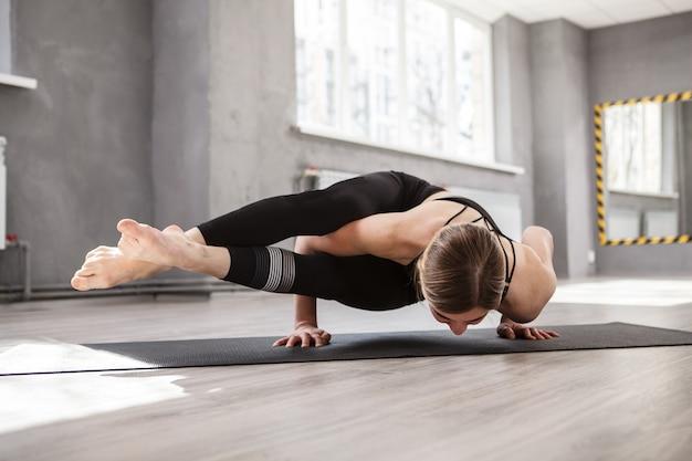 ヨガの練習をする強い運動女性、バランスの取れたアーサナに立つ
