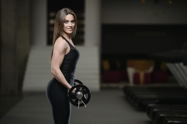 Strong athletic young girl working out in gym