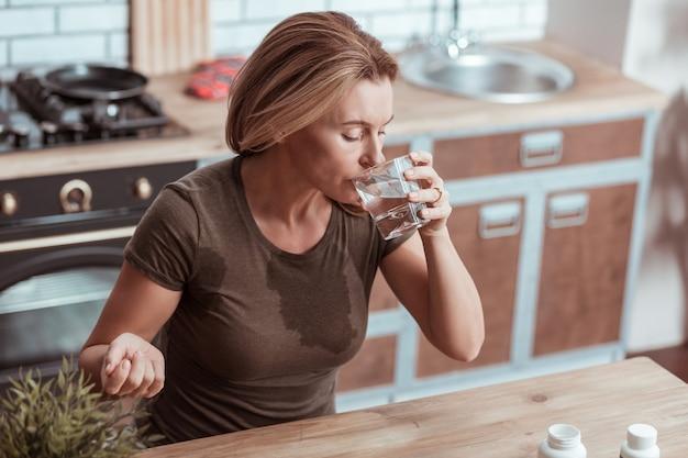 攻撃が強い。強いパニック発作の後に薬を服用しているtシャツに濡れたスポットを持つ金髪の女性