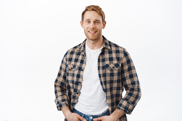 Strong attractive guy with ginger hair staring at front, posing over white wall