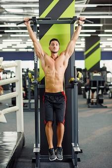 강한 매력적인 남자는 현대 체육관에서 훈련하는 동안 크로스바에서 풀업을 수행합니다. 전면보기.