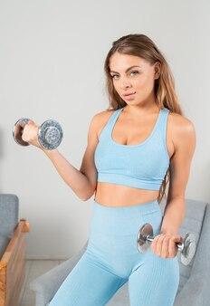 居心地の良いインテリアで自宅でダンベルを使ってエクササイズをしている強い魅力的な若いフィットの女性