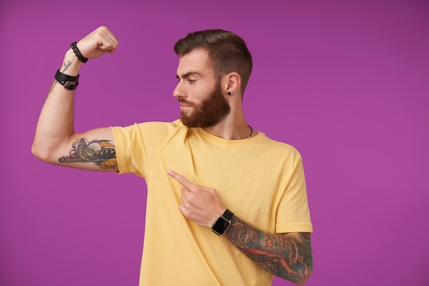 Strong attractive young tattooed male with beard and trendy haircut looking proudly at his hand and demostrating his biceps, standing on purple in casual t-shirt