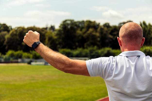 Strong bald men points to something in football field. back view of handsome man in t-shirt pointing.