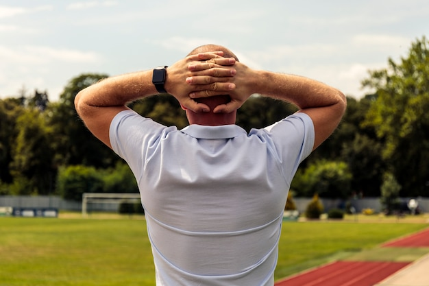 Strong bald men staying hand on head in football field