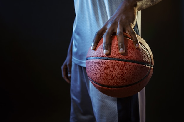 Strong basketball player hand holds ball in studio, black background. professional male baller in sportswear playing sport game, tall sportsman