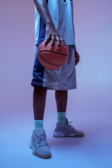 Strong basketball player hand holds ball in studio, neon background. professional male baller in sportswear playing sport game, tall sportsman
