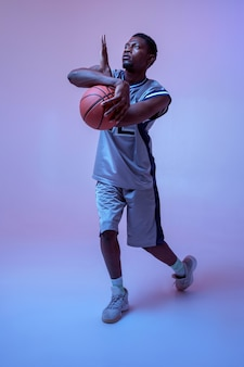 Strong basketball player hand holds ball in studio, neon background. professional male baller in sportswear playing sport game.