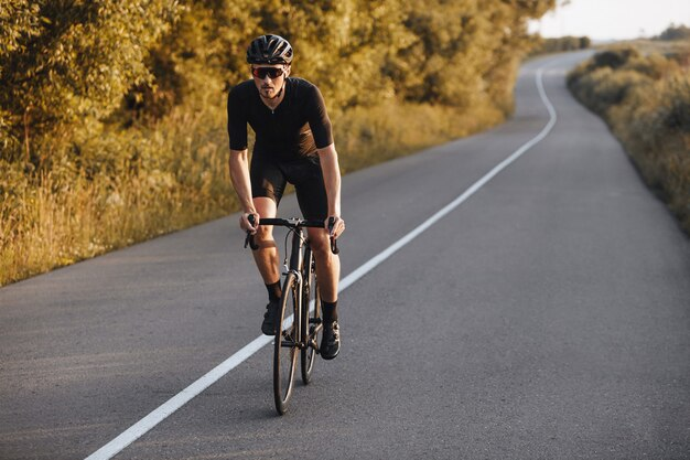 푸른 나무가있는 포장 도로에서 자전거를 타는 자전거 옷을 입은 강한 수염 운동 선수.