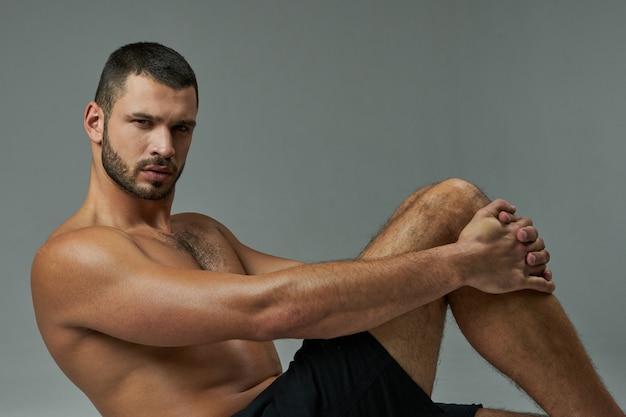 Сильный бородатый кавказский спортсмен в черных шортах позирует и смотрит в камеру изолированы