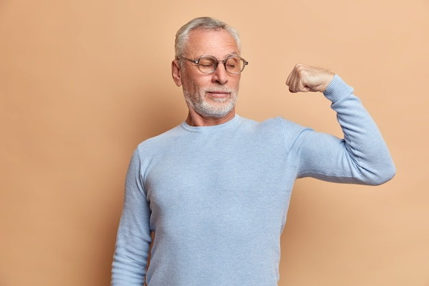 Strong bearded grey haired man pensioner shows biceps and stands with raised arm indoor wears jumper and spectacles says look at my strength demonstrates muscles isolated over brown wall