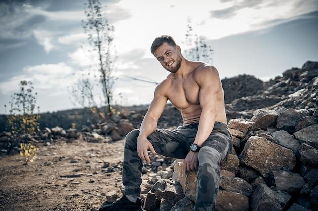 ミリタリーパンツの強いひげを生やした男。岩の上に座っているボディービルダー。裸の胴体。